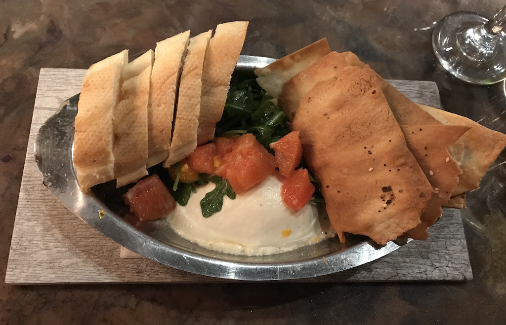 The Burrata topped with marinated oranges, arugula, black truffle honey, and is served with slices of baguette and everything flat bread.